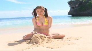 Buxom charming nympho wears bikini and poses on the beach